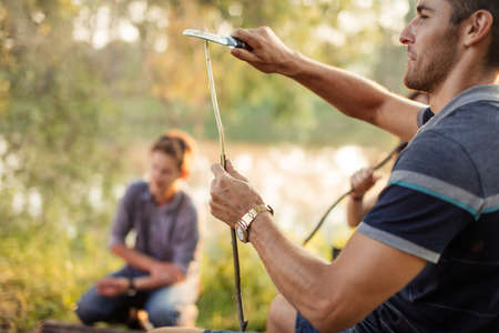 handsome beaded tourist is sharpening the tree branch to prepare food on the bonfire. close up side view photo. blurred background