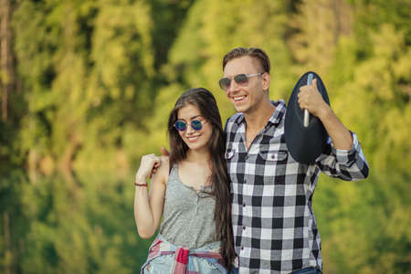 happy pleasant enamored man with a tape recorder on his shoulder is hugging his beautiful girlfriend. close up portrait