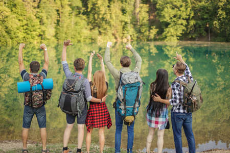 teenagers with rucksacks are arriving at the lake with beautiful nature. wildlife concept