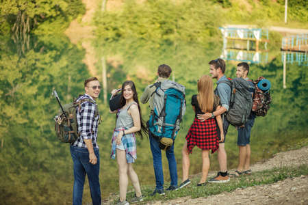 a positive couple of young people are posing to the camera while their friends are savouring the wonderful nature. back view photo. free time Foto de archivo