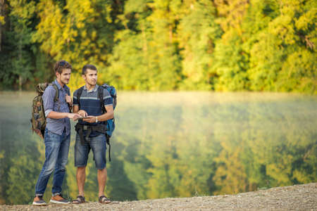 ambitious male travelers are using online tourist guide. copy space. vacation and holiday concept