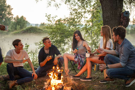 cheerful young people warming near the camp fire. warmth concept. unforgettable moments with best friends Stok Fotoğraf
