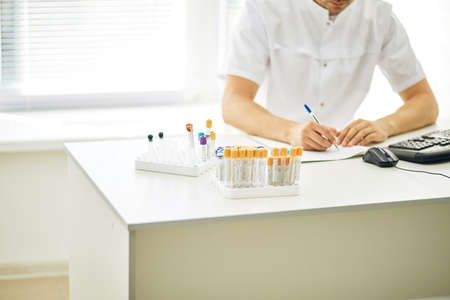 man writing the prescription after blood test. close up cropped photo. paper work at the hospital