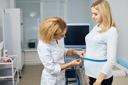 blond beautiful woman is being measured by a professional doctor in the hospital. close up side view photo. Banque d'images