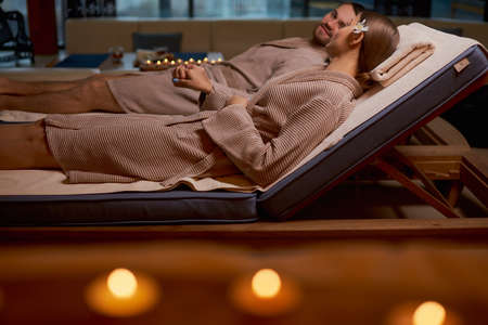 romantic place for taking rest of body and mind, young couple in love with each other, lying on bed in spa center together, get spa procedures with candles, relax