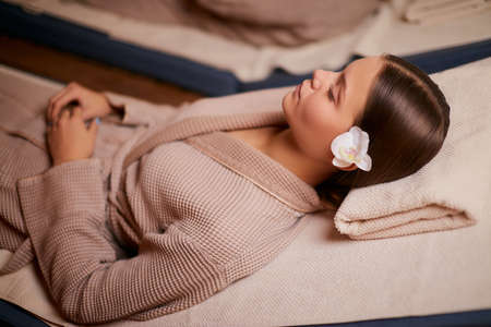 Attractive woman enjoy spending time in spa salon lying on bed in bathrobe and taking spa procedures. rest and comfort.