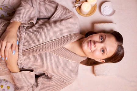 Attractive caucasian young woman in bathrobe look at camera, waiting for massage in spa salon. head on towel