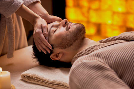 Spa, treatment concept. Young male wearing bathrobe lying on table with closed eyes and get massage by womans hands.
