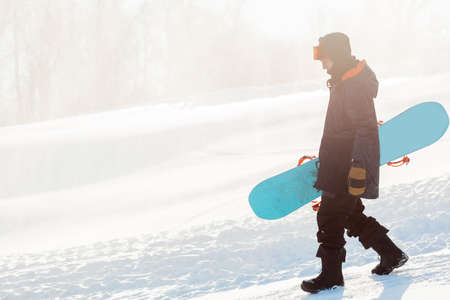 attractive man with a snowboard going down. side view full length photo. sportsman descending from the mountain