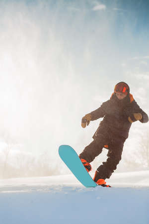 fearless snowboarder riding on a slope. active athlete is doing a trick. sportsman with a snowboard performing tricks