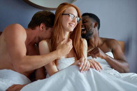 diverse trio making love in bedroom. sex party concept. redhead woman sit with two men, going to make love