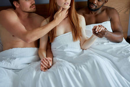 threesome concept. three diverse people going to have group sex together, one sexy woman and two men. polygamy or bigamy. swinger, orgy or trio having sex at home or in hotel