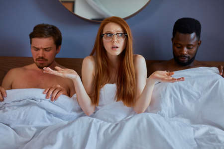 interracial couple having complicated affair and love triangle in bedroom, redhead woman at a loss