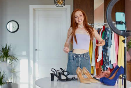 thinner girl shows how much she lost weight, young redhead female blogger share happiness with people, broadcast at camera with the use of light, at home. you can do it, just do it