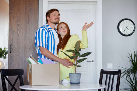 caucasian couple move in new apartment, they got keys from their new flat, happy. they enter room with boxes and plants
