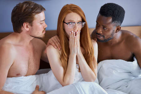 woman is molested by two men, she is shy and afraid. redhead woman have threesome sex on bed in hotel