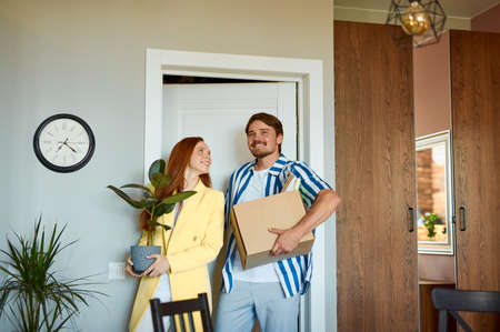 beautiful married couple enter new apartment, with boxes and plants. happy owners of new flat, stand smiling Stockfoto