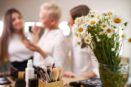 close-up photo of beautiful flowers in a vase, make-up artists in the background, discussing Foto de archivo
