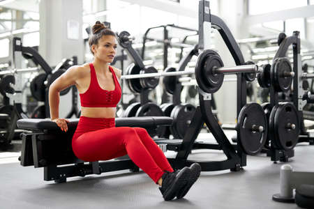 woman pumping legs doing squats in gym, in fitness center. attractive lady in red sportswear look side, concentrated on exercise