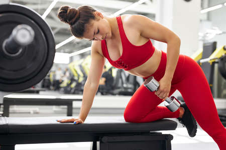 muscular fit female do exercises with weights in gym, in fitness center. strong woman shakes arm muscles