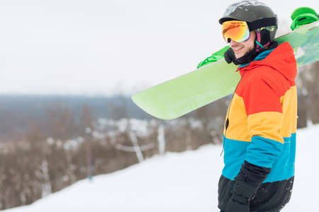 guy with positive mood preparing for snowboarding, side view photo. copy space