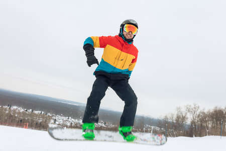 active guy is going to perform a jump at ski resort. full length photo, spare time, careless life, extreme sport