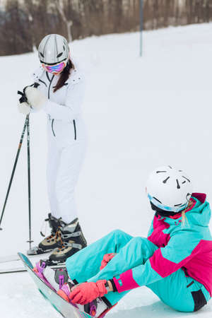 two awesome girls talking at the ski resort, conversation, girls having a chat outdoors
