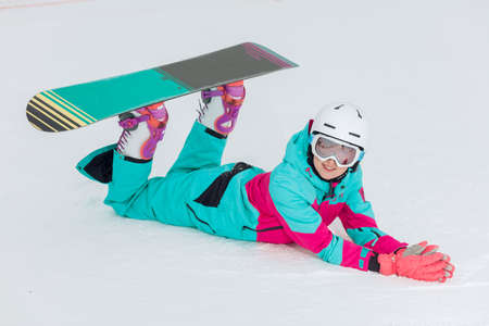 beautiful stylish girl with a snowboard resting on the snow, full length photo. free time, spare time, hobby Stok Fotoğraf