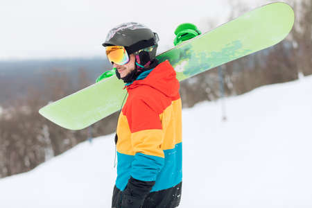 side view photo. sporty cheerful young man with a snowboard going for a walk.free time, hobby, lifestyle