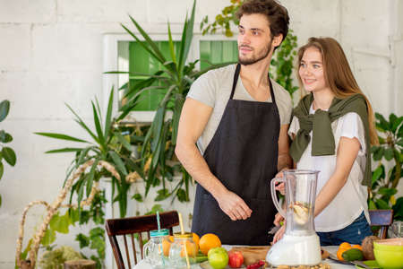 awesome cool joyful man and woman are looking aside while cooking.close up photo. friendly couple does everything togerther. copy space