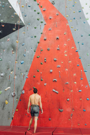 awesome man standing in front of the wall with grips for hands and feet. back view photo. sportsman thinking about climbing to the artificial mountain. guy having a rest after climbing