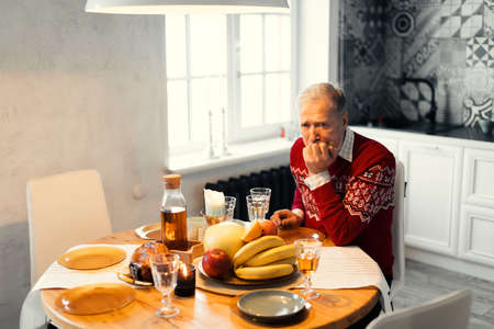 unhappy old man is waiting for his relatives. gey-haired man is celebrating Chritmas alone. Stock Photo