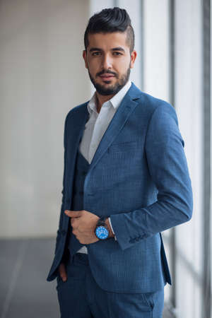 handsome bearded office worker in blue suit looking at the camera at workplace. profession, interest