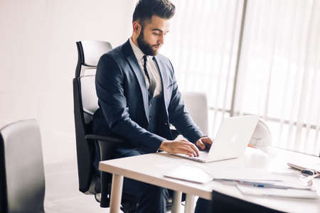 Young caucasian brunette businessman works in the office using portable computer. Business and career concept.
