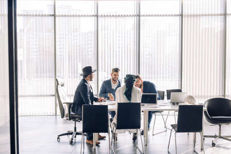 Elegant well-dressed business men of different age and ethnicity in suits gathered together for negotiating, collaborating in spacious modern office meeting room
