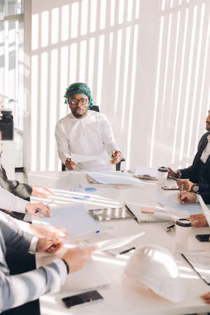 Multiracial group of experts headed by Arab leader, dressed in national white wear, analyzing business result and discussing profit.