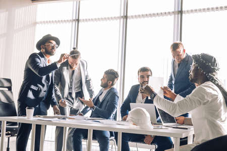 Hot debates. Group interracial business partners disagree with company CEO dressed Arab, on contract terms, people have dispute , using lots of hand gestures, but staing positive meeting in office
