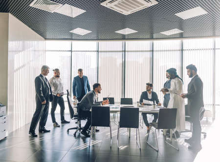 Multiethnic business men dressed in formal wear and national arabian clothes debating vivaciously in conference room. Conflicts can be resolved with a good joke, panoramic view. Archivio Fotografico