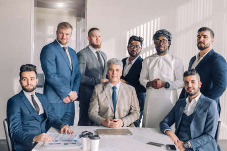 Diverse smiling business men gather at conference table together with his mature grey-haired leader, attending meeting or corporate briefing. African, indian and caucasian businessmen partners team. Stock fotó