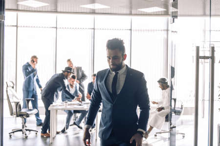 Young business man in formal suit leaving the boardroom with people conducting negotiations at table