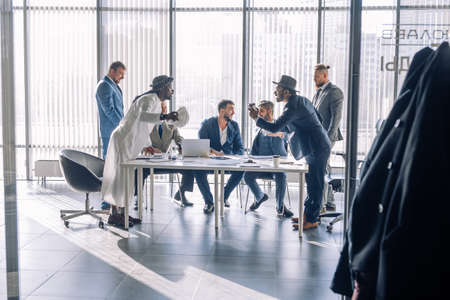 Two young Indian and Arabian business partners interacting, argue passionately, having positive mood, standing opposite each other in office with big panoramic window and co-workers, sitting at table Banco de Imagens