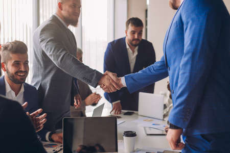 Business people in formal wear shaking hands, finishing up a meeting, establishing multi-ethnic partnership, making deal. Banco de Imagens
