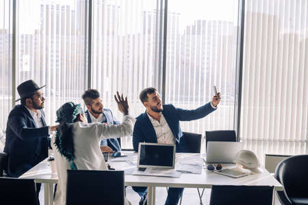 Positive caucasian bearded businessman taking selfie with his middle eastern and indian partners during workday, sitting in conference room.