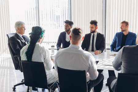 Mature grey-haired financial director reporting to his multiracial top management co-workers of income increase for this year, showing graphs with results of successful teamwork