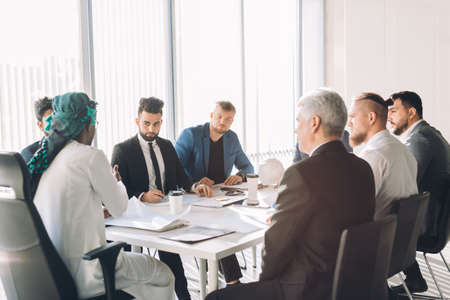 Arabian investor in white national candura and gutra on head discussing company financial strategy with his multirucial male managers during meeting at desk in office.