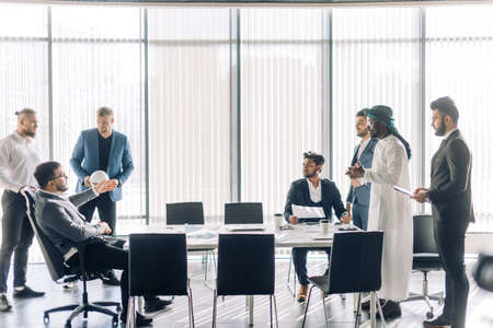 Debates or business solution concept. Multiracial business men in Arabian white national and formal European black clothes disputing at a meeting while sitting opposite each other at the modern office