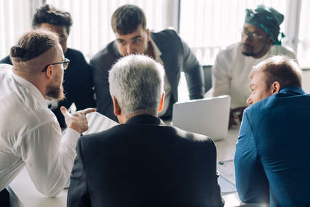 startup business, serious multiethnic business people of different age and races gather in meeting room in white modern office interior.