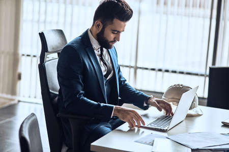 Elegant businessman working with laptop. stylish bearded guy is typing a document at workplace. man sending messages