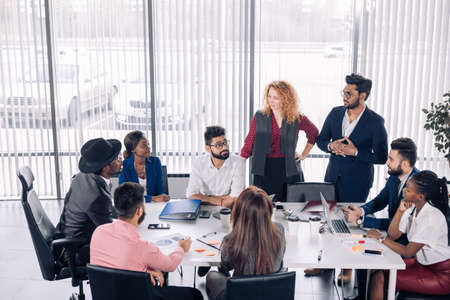 African corporate business coach explains basic principles of corporate strategy to diverse mixed-race employees at their first meeting at conference room.