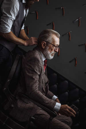 Barber brushes grey hair of respectable old male client dressed in tailored suit in the barber shop. Handsome barber makes new hairdo while a rich old man smoking cigar and drinking wisky.
